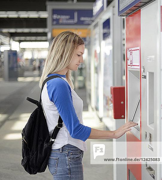 Blond woman using ticket machine at train station