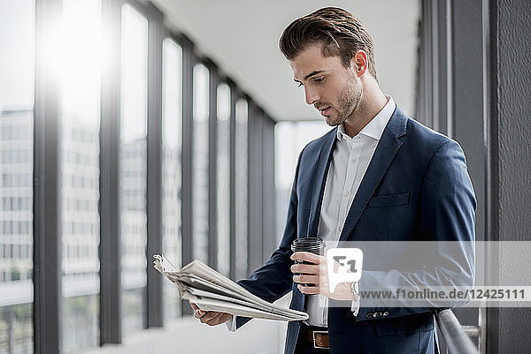 Young businessman standing in a passageway with takeaway coffee and newspaper