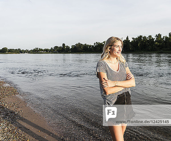 Blond woman at riverside in the evening