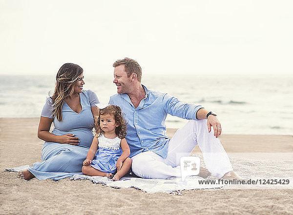 Family sitting on blanket on beach Family sitting on blanket on beach