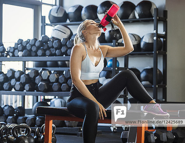 Young woman drinking in gym