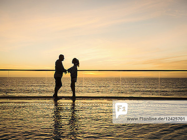 Couple at poolside over sea
