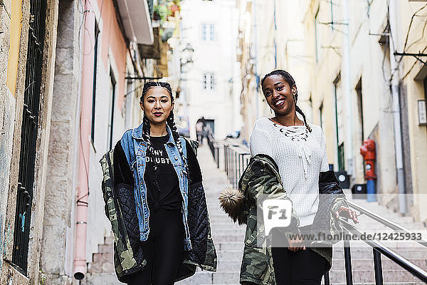 Portugal  Lisbon  Two smiling young women walking outdoors