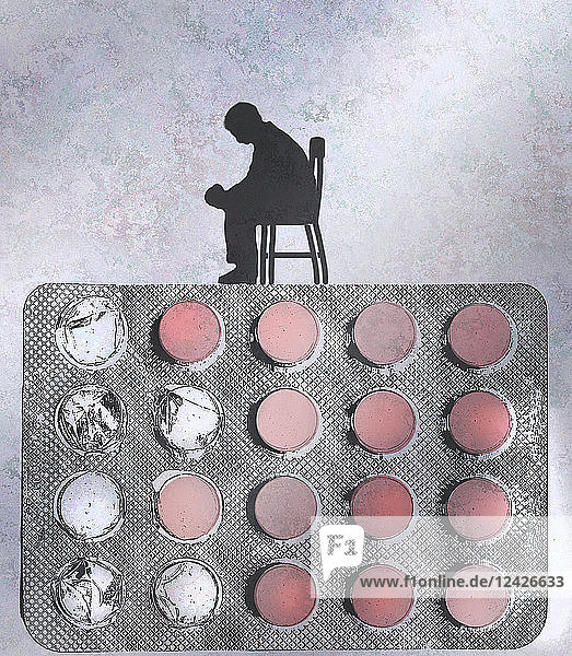 Depressed man sitting on top of pill blister pack