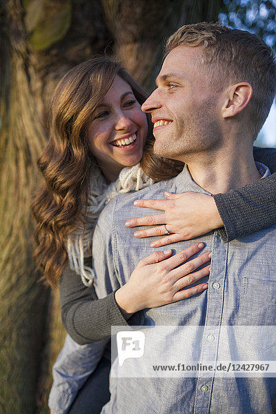 Smiling couple in love with woman embracing man from behind