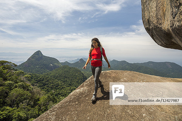 Front view of single female hiker hiking on rocky peak with view of mountains  Atlantic Rainforest  Tijuca Forest National Park  Rio de Janeiro  Brazil