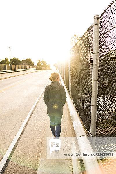 Rear view of single woman walking on overpass