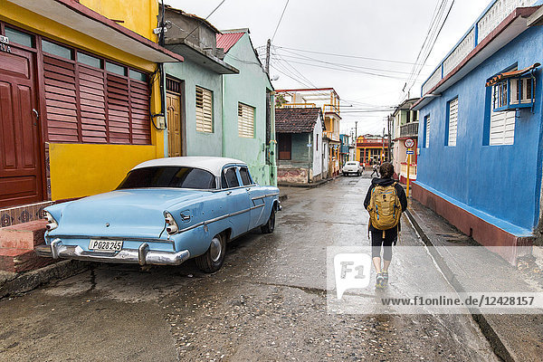 Rear view of female tourist walking on street by vintage car in Baracoa  Guantanamo Province  Cuba