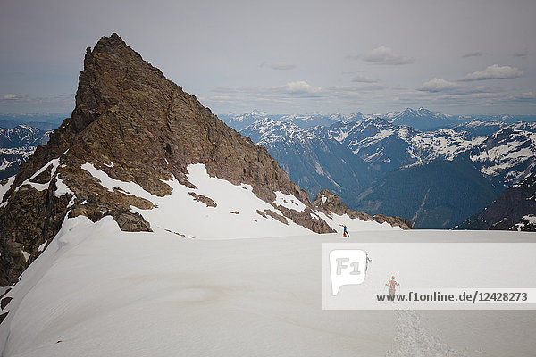 Distant view of three climbers approaching Foley Peak in the North Cascade Mountain Range  Chilliwack  British Columbia  Canada