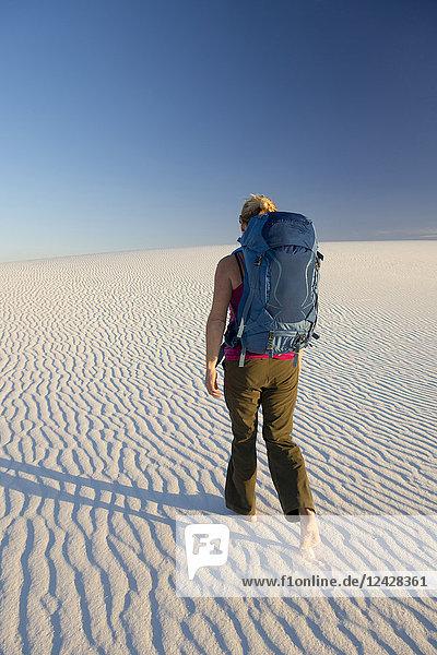 Rear view of female backpacker hiking in desert of White Sands National Monument  Alamogordo  New Mexico  USA