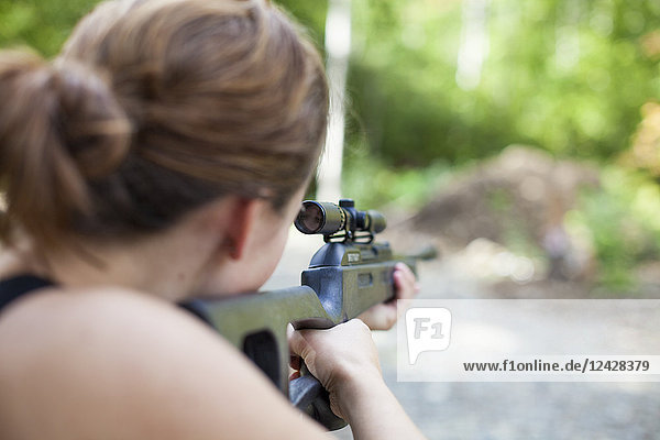 Over the shoulder view of woman aiming with rifle