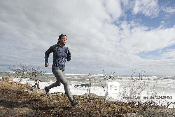 Side view of single woman trail running along coast of Maine  USA