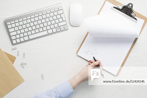 Hand mit Kugelschreiber  weißes Papier und Tastatur