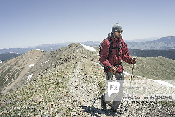 Front view shot of male backpacker hiking on Wheeler Peak  highest point in New Mexico  Taos  New Mexico  USA