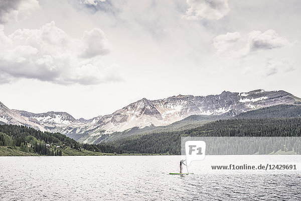 Distant view of single adventurous man paddleboarding on Trout Lake  Telluride  Colorado  USA