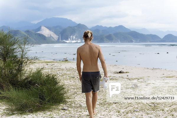 Rear view shot of single shirtless man walking on beach  Banda Aceh  Sumatra  Indonesia