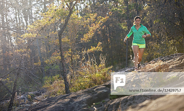 Front view shot of single woman trail running in forest  Moss Rock Preserve in Hoover  Alabama  USA