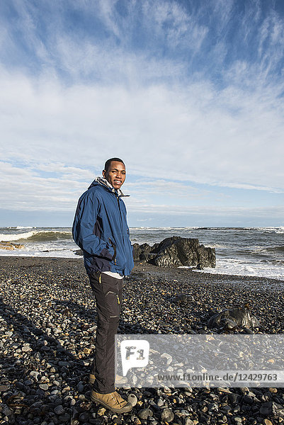 Portrait of an African American man standing on rocky beach
