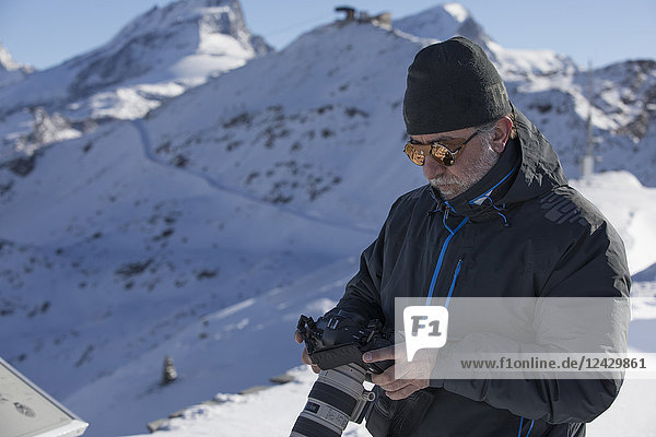 Waist up shot of photographer with camera in Swiss Alps in winter  Zermatt  Valais Canton  Switzerland
