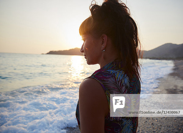 Head and shoulders portrait of beautiful young woman on beach at sunset