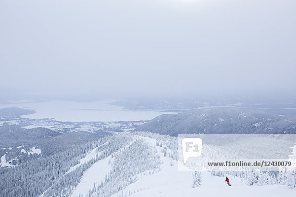 Distant view shot of woman skiing in mountains with Lake Pend Oreille in background  Sandpoint  Idaho  USA