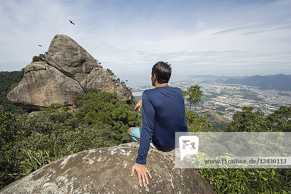 Rear view of single man sitting on rock in natural setting  Tijuca Forest  Rio de Janeiro  Brazil
