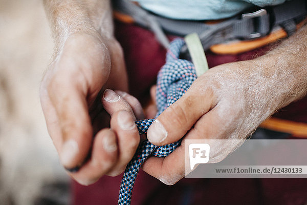 Close-up of hands of rock climber tying climbing rope to waist