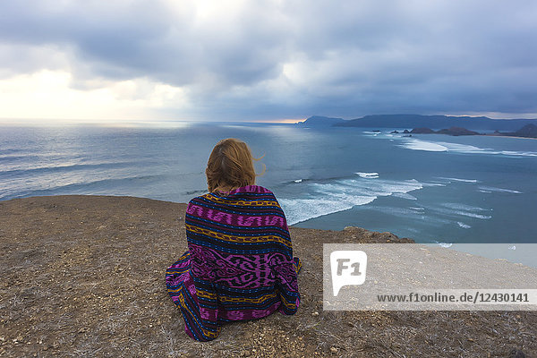 Rear view shot of single young woman wrapped in blanket sitting on cliff near ocean  Kuta  Lombok  Indonesia