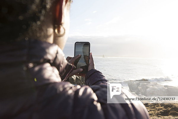Over the shoulder view of single African-American woman taking picture with smartphone on seashore