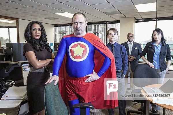 Kaukasischer Superheld mittleren Alters und sein gemischtrassiger Teamstab in ihrem Büro