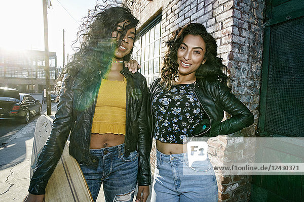 Zwei junge lächelnde Frauen mit langen lockigen schwarzen Haaren stehen auf dem Bürgersteig  halten ein Skateboard in der Hand und schauen in die Kamera.