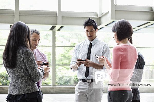 Eine gemischtrassige Gruppe von männlichen und weiblichen Geschäftsleuten  die im Lobbybereich eines Kongresszentrums stehen und ihre Mobiltelefone benutzen.