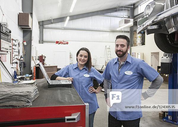 Ein Porträt von zwei kaukasischen Mechanikern und Mechanikerinnen in einer Antiquitätenwerkstatt.