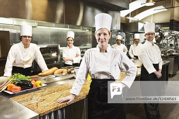A portrait of a Caucasian female chef and her team of chefs in the background.