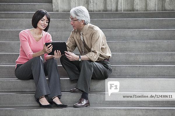 Eine hispanische Geschäftsfrau und ein asiatischer Geschäftsmann arbeiten an einem Notebook  während sie auf den Stufen eines Kongresszentrums sitzen.