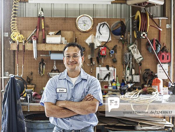 Hispanischer Arbeiter im Werkstattbereich eines Landschaftsbauunternehmens.