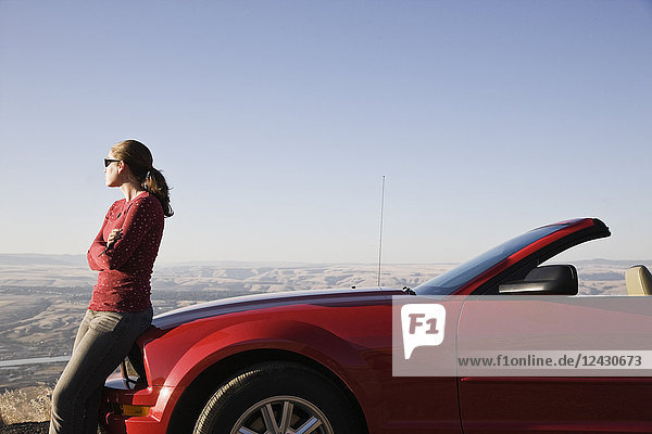 A young Caucasian woman leaning on her convertible sports car at a rest stop.