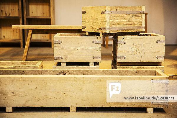 Stapel von Holzkisten in verschiedenen Größen in einem Lagerhaus.