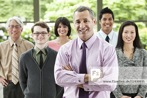 A portrait of a mixed race team of business people with a Caucasian businessman in the lead.