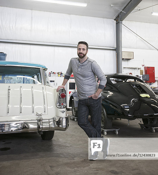 A portrait of a Caucasian mechanic in his classic car repair shop.