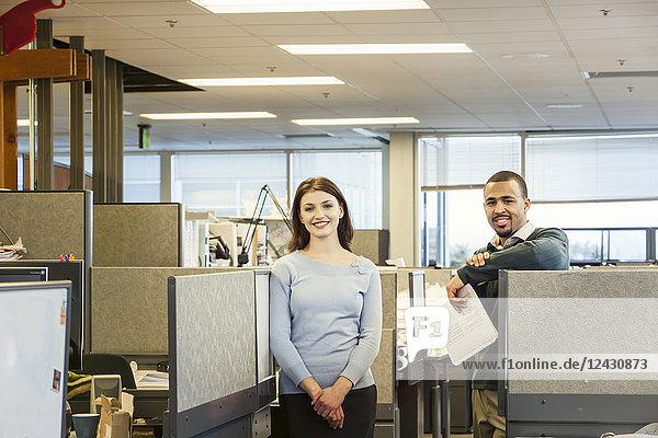Ein Porträt einer jungen kaukasischen Geschäftsfrau und eines schwarzen Geschäftsmannes in ihrem Firmensitz.