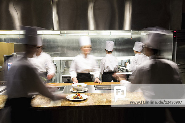 A blurred view of a crew of chefs working around a commercial kitchen.