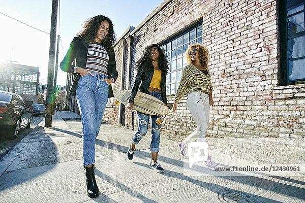 Drei junge Frauen mit langen lockigen Haaren gehen auf dem Bürgersteig  eine trägt ein Skateboard.