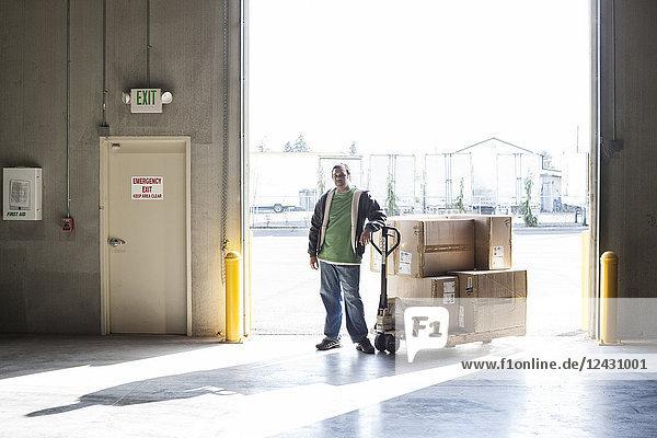 Männlicher Lagerarbeiter  der in einem Vertriebslager neben einem manuellen Palettenhubwagen und Kartons steht.
