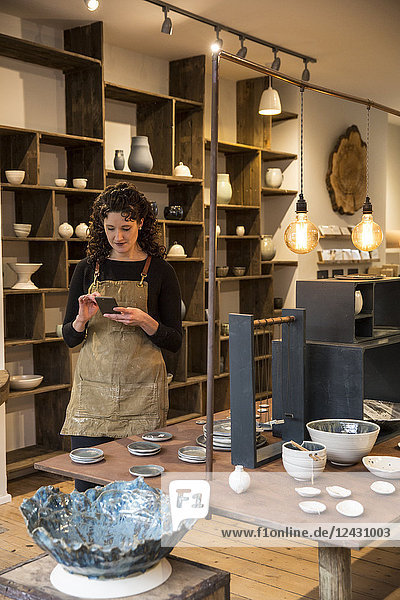 Woman with curly brown hair wearing apron standing in her pottery shop  looking at mobile phone.