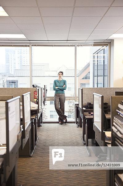 Das Porträt einer jungen Geschäftsfrau  die an einem Fenster in der Nähe von Kabinen in einem Firmenbüro steht.