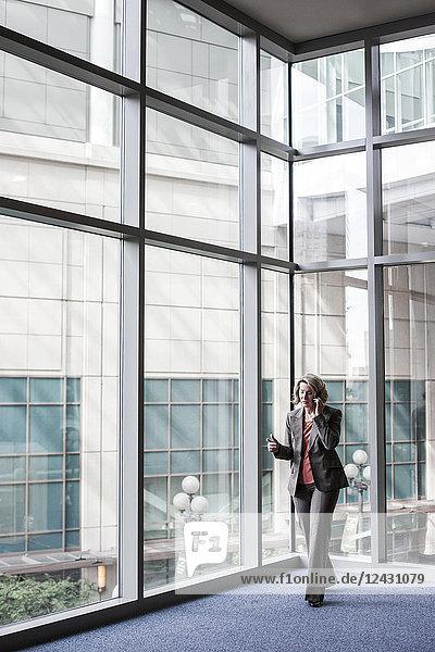 Eine kaukasische Geschäftsfrau  die mit einem Mobiltelefon telefoniert  während sie neben einem großen Fenster in der Lobby eines Kongresszentrums steht.