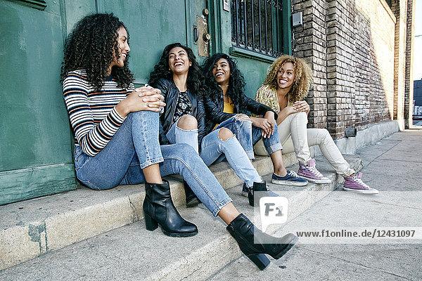 Vier junge Frauen mit lockigem Haar sitzen nebeneinander auf Stufen vor einem Gebäude.