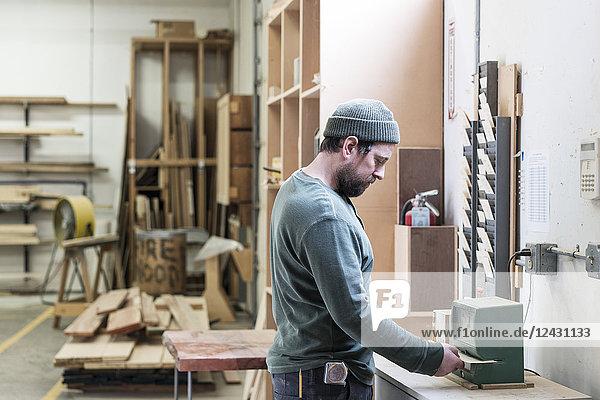 Ein kaukasischer Zimmermann meldet sich mit einer Stechuhr in einer holzverarbeitenden Fabrik.