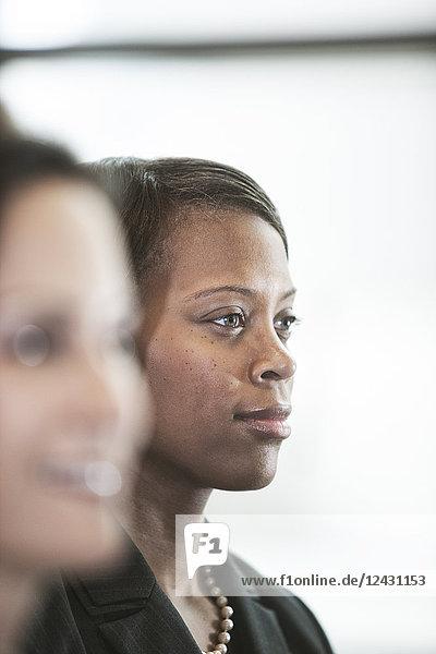 Das Porträt einer schwarzen Geschäftsfrau  die an einem Fenster in der Lobby eines Kongresszentrums steht.